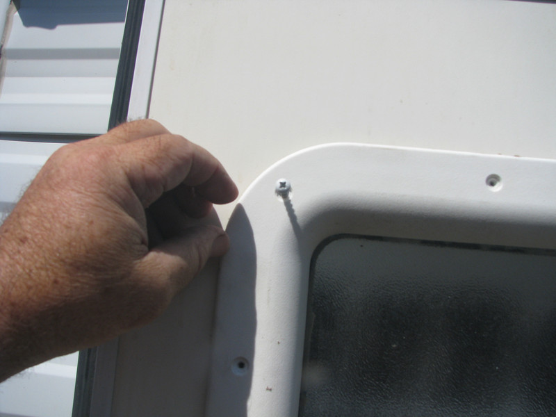 Placing the inter flange in window openning and hand starting the screws.