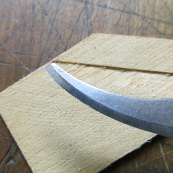 This curved knife was modified to convert the tool into a saw. This is an old watchmakers trick, they would put teeth on a double edge razor to convert the sharp blade edge into a saw. Once a wood handle was applied to the blade they would use it to saw a small kerf on a shaft for terminating the mainspring. This tool can be used for scoring or pre scoring the wood where it would traditionally be done with an exact o knife or layout knife. The advantage is you are now sawing the wood thus reducing the probability of the blade from following the wood grain. The control with this miniature veneer saw is so good you will seldom need a straight edge . To form the teeth in most any sharp knife edge blade you install the blade in a machine vise with the edge up. Next lay one flat of a three sided small triangle file on one edge and slightly tap the file. This will swedge teeth into the blade, rotate the file and retapp until you cover the required length. Last swipe both sides of the blade with a hard Arkansas stone to remove metal that was forced out of the saw gullies.