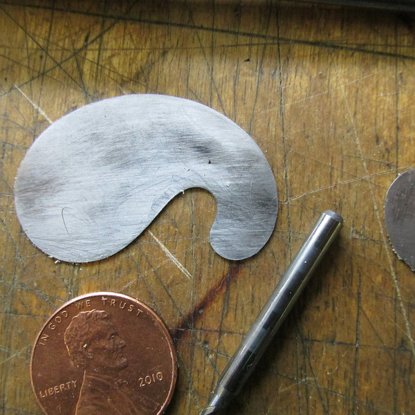 Two small French curves. The carbide drill is used to turn or refresh the burr around the French curve scraper. Place the drill in a Dremell tool backwards so the shaft is showing. With a light dab of fine oil on the carbide shaft and the tool rotating fast you can hold the blade and walk the shaft around the curve to turn a burr, hold the shaft at 5 to 10 degrees off the perpinduclar edge. When forming the burr apply strong pressure to keep the rotating carbide in contact.