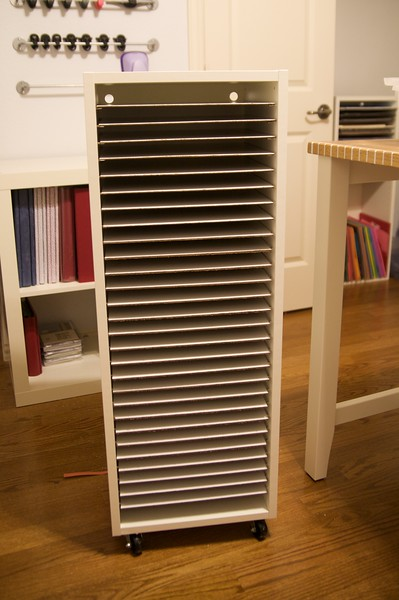 """My new paper storage.  I bought an Ikea upper cabinet (size 15x39"""") base (item 443.832.10) for a shell for my storage solution.  Then, I went to the hardware store and bought two 1/8""""x4'x8' panels.  I purchased the cheapest white panelling they had, though they sell slightly more expensive and slightly thicker bead board in the same section.  I had them cut each piece to 11 1/2""""x13 3/8"""".  I was able to get 28 shelves out of one panel, which is exactly what was needed for this cabinet (I bought 2 cabinets to hold my paper.)  Using panelling serves two purposes.  1.  Price - it's a cheap material and can be cheaper if you don't mind brown, but I wanted white.  2.  It is thin, but sturdy.  Regular shelves are 3/4"""" thick each...that's space I could be using for paper!!   I built the cabinet, then attached casters (hardware store) to the bottom so I can easily shift it from my closet behind the doors to protect from dust and light to next to my work space.  Then, using pegs I bought at the hardware store (check Ikea's spare hardware section by returns for cheaper option, I didn't realize how pricey these little things would be at the hardware store), I mounted a peg in every...single...hole except the very top and very bottom and rested a shelf on each set of 4.  A tip from someone who's been there:  BEFORE constructing the cabinet, nail in all 112 pegs in the holes provided, THEN build the cabinet so you don't fight gravity and the tight space.  When stacked with paper, the shelves barely show, as the paper sticks out 1/2"""" in the front and the shelf is only 1 3/8 inch wider than each sheet.  I'll post a picture soon with it filled with my paper and explain how I organize it."""