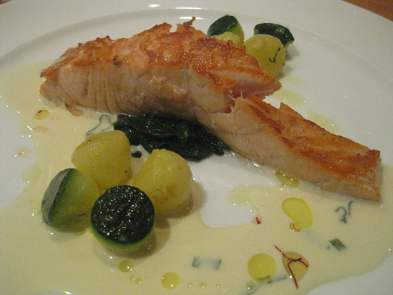 salmon steak on a bed of spinach with succini/courgette