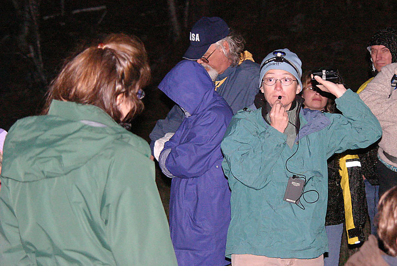 Participants ponder the sound of an owl call as Nancy preps the group for a trek up the draw, where the group would try to hear a responding owl call.