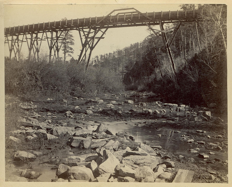 Bierce was eventually able to convince the company to buy out West's contract, eliminating a major distraction for Bierce in trying to complete the flume.  Alas, short of capital and under much criticism himself, Bierce saw the August deadline come and go.  The flume was still not done.<br /> <br /> There were also many trestles that elevated the flume as high as 80 feet.  <br /> <br /> The flume itself was 42 inches by 48 inches and was made of wooden planks tied together about every four feet.<br /> <br /> Photograph courtesy of the Minnilusa Historical Association.