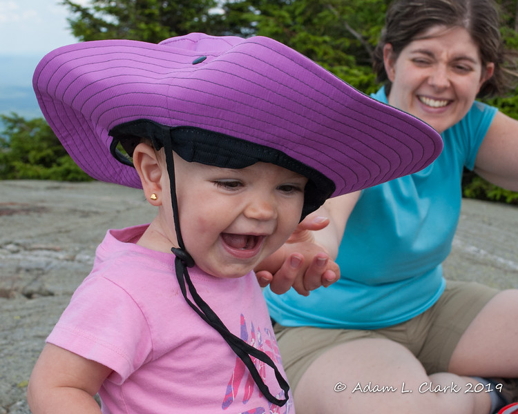 A happy smile while wearing her sister's sun hat