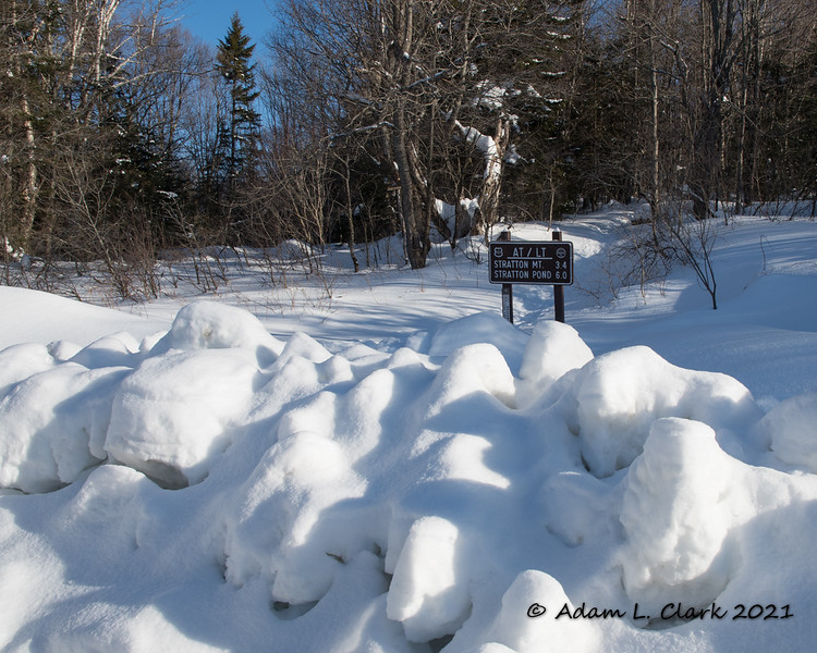 The trail sign for the start of the hike behind the snowbank at the parking lot