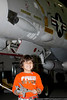 Zachery Qureshi (Age 5) of Great Neck, with his F-14 model in front of the museum's F-14, following the Make & Take Program at the Cradle of Aviation Museum, conducted by the Long Island Scale Model Society.