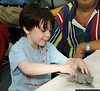 Blake Goldberg (Age 5), works on a plastic model at the Make & Take Program at the Cradle of Aviation Museum, conducted by the Long Island Scale Model Society.