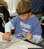 Joseph Vnook (Age 10) of Bayville, works on a plastic model at the Make & Take Program at the Cradle of Aviation Museum, conducted by the Long Island Scale Model Society.
