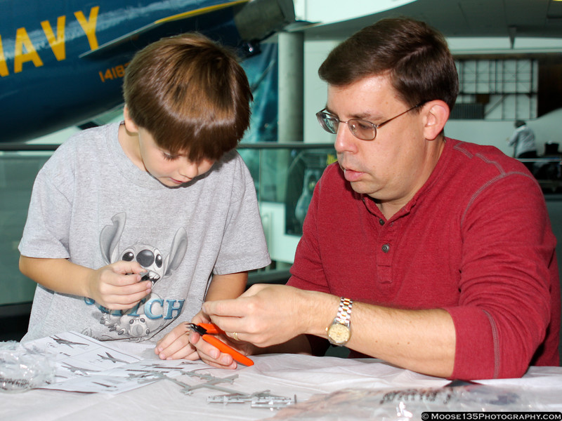 Greg (Age 11) and Rainer Burger of New Hyde Park, working on a plastic model at the Make & Take Program at the Cradle of Aviation Museum, conducted by the Long Island Scale Model Society.
