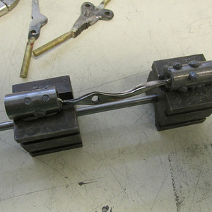The 1/2 inch ends were filled with a special heat sensitive fixture plastic I use for holding odd shaped parts while hand engraving. Using a hair dryer I heat the plastic and set the attached rods inside. The 2 vee blocks provide registration for the spin fixture and tail stock. The plastic stuffing material sets rock hard in about 5 minutes.