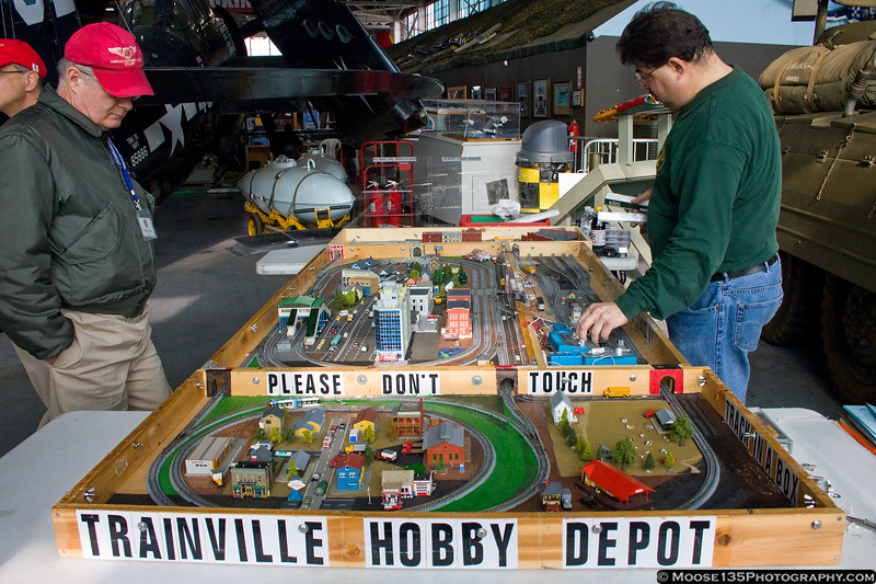 Joel Berse of Trainville Hobby Depot demonstrates his model railroad layout at the American Airpower Museum, while museum volunteer Gerry Kenna looks on.