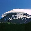 "Fantastic lenticular cloud formation surrounds the classic cone shaped volcanic summit of 11,239 ft Mt Hood in Oregon. Photo credit to Dennis Stilwell ""nwhiker.com"", courtesy of the summitpost.org website, taken in summer 2001."