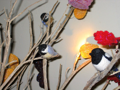 Collection of wool birds and felt leaves displayed on branches.