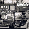 """Robbert / PA3BKL in 1985.... (I was 29 here, sun-tanned, just came back from Florida USA). <br /> QTH: Culemborg (JO21OW)<br /> Drake Line (TR7 + MN7, and R7 + MN77) [sold the complete Drake-line to EA3NJ in 2009]. <br /> Kenwood TR-7800 (Mobile set: 2 meters FM). ICOM IC-120 (23 cm FM).  Kenwood TS-770E (Base: 2 m/70 cm, FM/SSB/CW).<br /> The 'keyboard' there is the notorious TONO-9000E: a great RTTY unit (for that time!! but the RTTY signals sounded 'clicky', I added some filters as a mod). <br /> See also the great AMT-2 (Amtor), on top of the TRIO Oscilloscope. To the left of the scope: a Takeda Riken Spectrum-Analyser, in that time very popular among the CAI builders in the Netherlands. Suddenly many local FM pirates came to our house with their (ILLEGAL) transmitters and asked if I PLEASE could check if their (illegal) FM modulated spectrum was 'clean', ha ha!!<br /> Just to the left of my nose you see a 'Big Boomer'. It was a Linear Amplifier (tubes!!), a '200 Watt booster' for the 27 Mhz 'Citizen Band'.<br /> The (Dutch) licenced radioamateur community was quite upset that I (as an official licenced amateur) 'dared' to appear on the cover of Radio Amateur Magazine [RAM] next to 'that thing for citizenband pirates...'. Hey guys: MANY of us STARTED the hobby with 27Mhz!!! It is NO SHAME!!<br /> (Camera: CANON A1 !!!!!, but this photo had to be scanned in, as ... the A1 was NOT digital, folks. Check out that camera here: <a href=""""http://tinyurl.com/5vou9nx"""">http://tinyurl.com/5vou9nx</a>)"""
