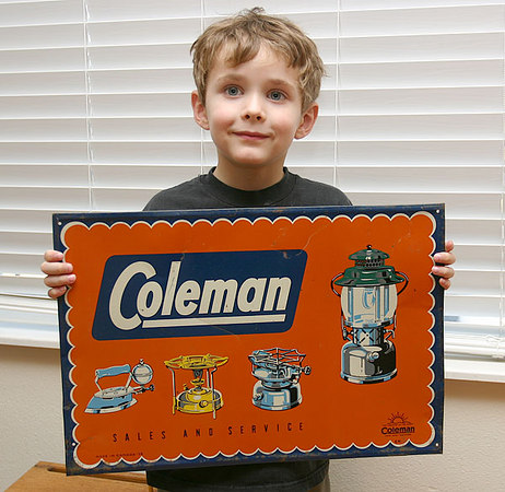 Jacob holds an old advertising sign for Coleman lanterns & stoves.  Neat old graphics - I believe this is silk screen on tin.