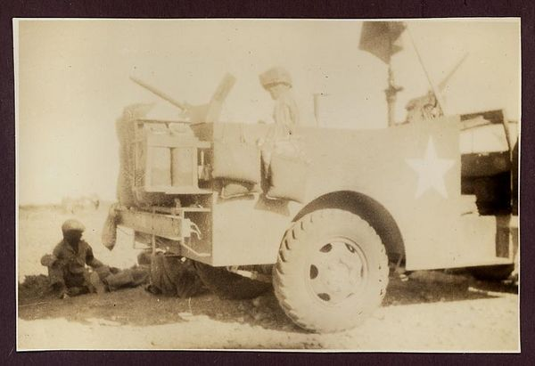 1942 photograph depicting a Scout Car of the 3rd Armored Division which is mounted with a machine gun. A few soldiers seen as well. The photo taken while the Division was training in the Mojave in July 1942