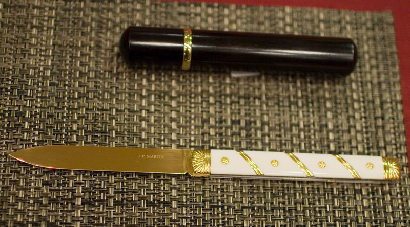 Jean-Pierre Martin folder with a gold(en?) blade, inspired by traditional antique French knives.  The cylinder above is the pocket sheath for the knife.