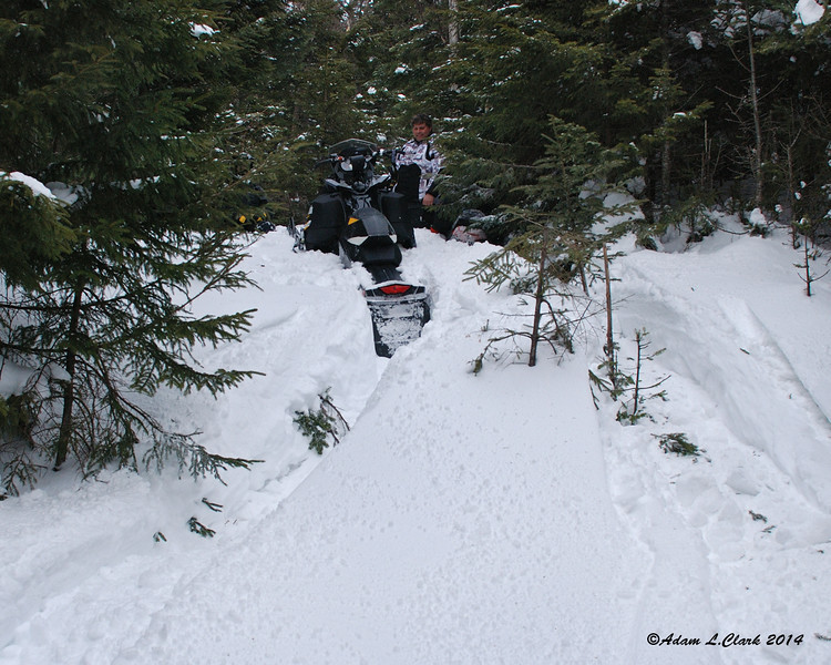 David (in the trees on the left) got stuck and Jim tried to still get by.  His sled is hiding in the trees on the right stuck