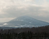 A closer look at the mountain that appears to have some snow covered trees on top