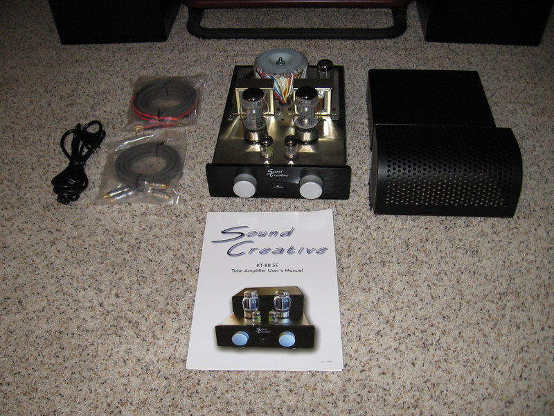 The Sound Creative KT88 SET amplifier comes with a removable tube cage, a pair of speakers cables, a pair of interconnects, a power cord, and the manual. It is shown here with the tube cage and the transformer covers removed for inspection.