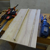 Each of the longer slats can be trimmed one inch and used as a side panel brace. They should be positioned about halfway between the front and back panel recesses and their position should be marked with a pencil so pilot holes can be drilled in the side panels for three screws that will hold them in place while the glue dries. The side slats are pre-cut at an angle that sets their front surface parallel to the front and back panels.