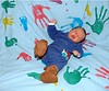 Jake Finneas Twomey drops in, caught by quilt. Footprints by Tucker and Izzy. Handprints by Tessa, Pat, Matt, Lisa, Christopher, Tara, and Sylvia