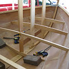 Prior to installing the stringer, deck beams are fitted and later notched for the stringers and also for a king plank that runs down the centerline.  Bulkheads are fitted to the deck beam and the floor below it, and together with the deck the forward and after ends of the boat are enclosed to provide buoyancy in the event of capsize.