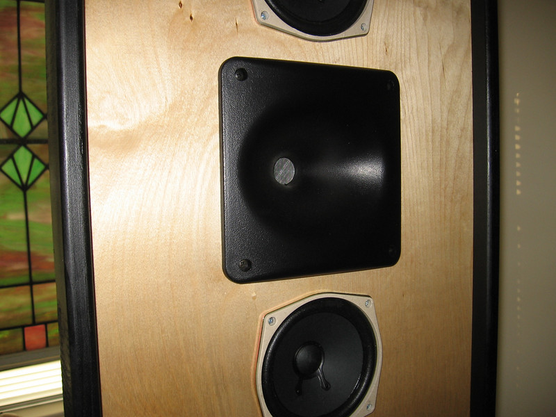 A close up view of the Dayton waveguide tweeter and one midwoofer also shows the attractive grain pattern of the Baltic birch veneered baffle. The baffle is finished with two coats of tung oil, and the side rails are painted satin black.