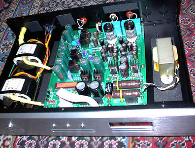 "The Lite Audio DAC-60 comes stock with two R-core power transformers, six separate regulated power supplies, dual Burr Brown 24/96 DAC chips, discrete components in the analog filter section, and a two tube EH6922 output section. Here's a ""before"" picture. In this picture one upgrade has already been completed: The large Hammond choke to the right of the circuit board has replaced a resistor between the power supply caps, and I also installed some chassis damping material. (The stock coupling caps are the aqua color rectangular parts behind the tubes)."