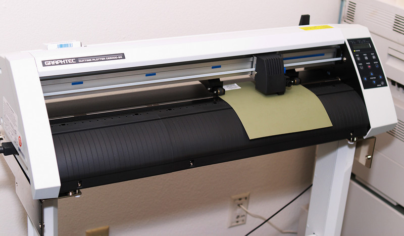 """My Graphtec CE5000-60 24"""" vinyl cutter with a sample sheet of Oracal 631 wall vinyl loaded and in the process of cutting a dragon design."""