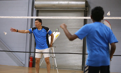Badminton coach Andy Chong of Acton and young players at Mill Works in Westford. Chong pulls birdies out of the feeder tubes to toss for players including Advikar Ananthkumar, 12, of Boxboro, right.(SUN/Julia Malakie)