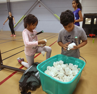 Badminton coach Andy Chong of Acton and young players at Mill Works in Westford. Dia Mysore, 7, of Littleton, left, and Pranav Katragadda, 10, of Westford, pick out birdies to hit. They've been to badminton camp before this class. (SUN/Julia Malakie)