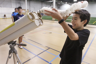 Badminton coach Andy Chong of Acton and young players at Mill Works in Westford. Chong's son, Kai Chong, 12, of Acton, feeds birdies back into tubes where they can be pulled out easily to toss or hit.(SUN/Julia Malakie)