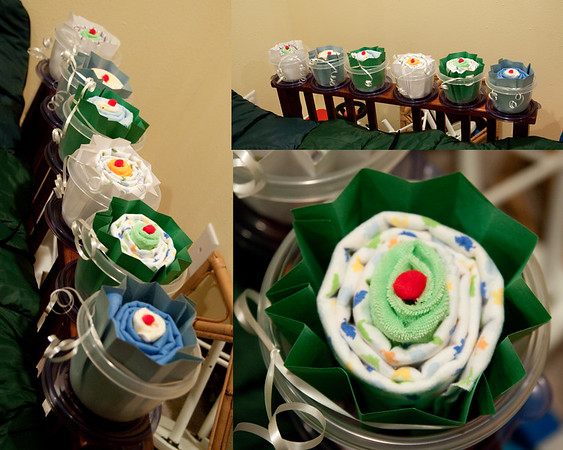 I made these for my sister's baby shower.  I didn't just want to have decorations on the tables that we would throw away at the end of the day.  I made these cupcakes out of a baby blankets and washcloths, something for my sister to take home as a gift.  I used cardstock and folded it back and forth to look like a cupcake wrapper.  I tied them with string to hold them together and placed them in reusable/throw away dishes.<br /> Also for decorating I made a clothesline with twine and hung up some new outfits for my sister's twins.<br /> Pictures aren't great here.  I had to keep these in a storage area so my lovely children would not destroy them.