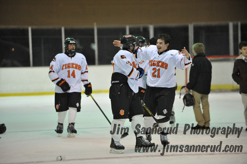 Mike Lotito #21 celebrates with teammates after the victory. White Plains High School Tigers varsity ice hockey team upset the defending NY State champion Suffern Mounties 3-2 in overtime at Ebersole Ice Rink on Thursday, December 6, 2012