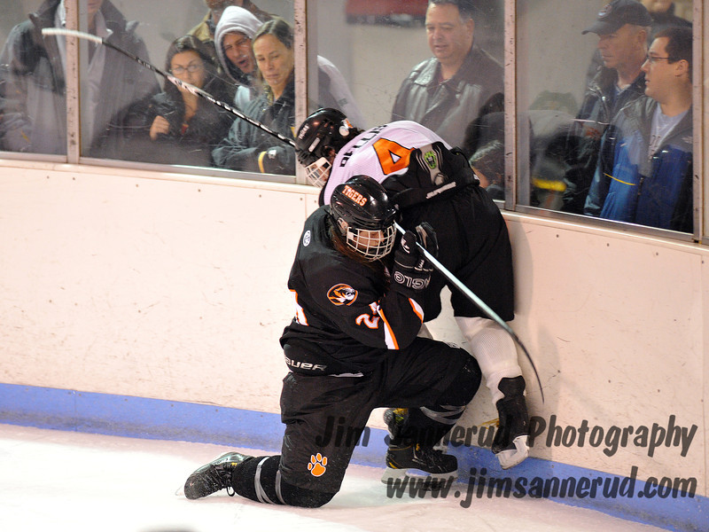 White Plains Kelsey Fee #24 pins #4 Ted Bellis to the boards behind the White Plains net. White Plains High School Tigers vs. Mamaroneck Tigers Varsity Ice Hockey at Hommocks Park Ice Rink, Friday, December 21, 2012, White Plains lost 3-1