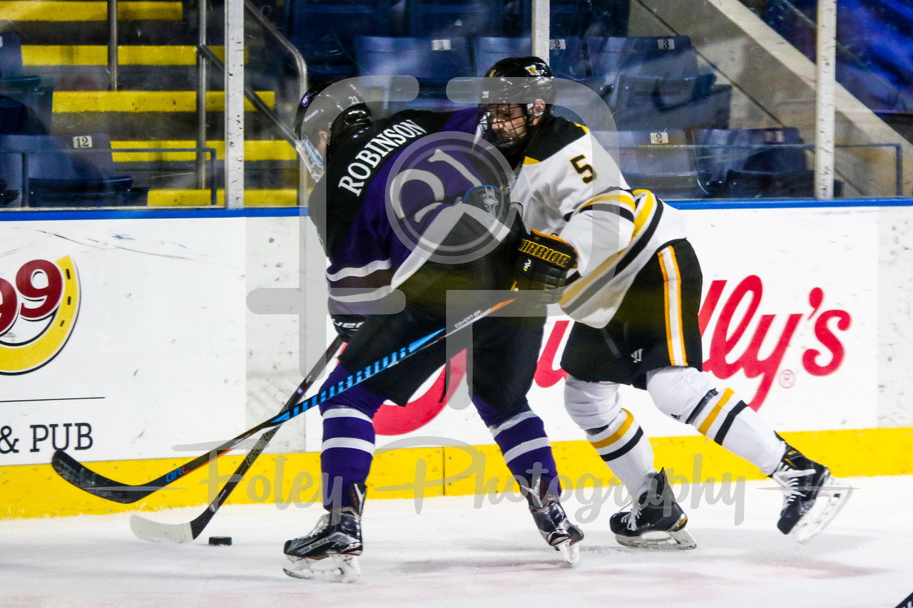 Holy Cross Crusaders forward Neil Robinson (21) American International Yellow Jackets defenseman Ryan Polin (5)