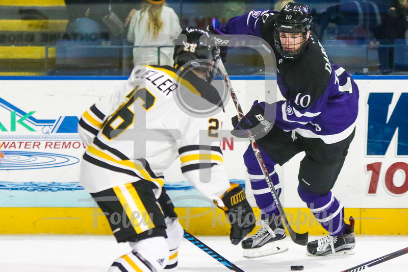 Holy Cross Crusaders forward Kevin Darrar (10) American International Yellow Jackets defenseman Johnny Mueller (26)