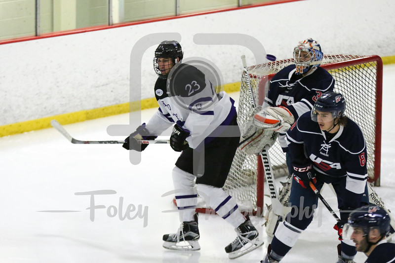 Holy Cross forward Ryan Ferrill (23) USA Hockey National University Team goalie Joe Olen (University of Illinois) (31)
