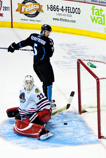 Blake Geoffrion watches as the puck slides through Rockford goalie Hannu Toivonen's pads