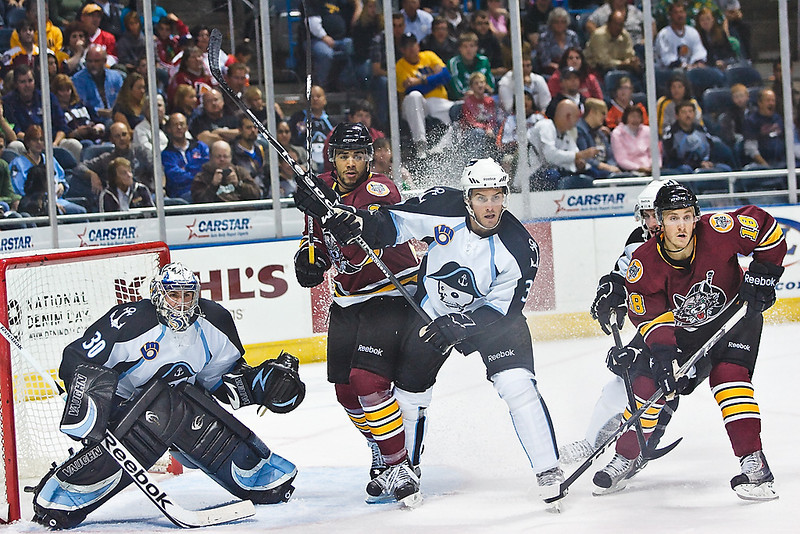 Chicago Wolves Darren Archibald (left) attempts to gain position in front of the net behind Admirals defenseman #3 Jeff Foss