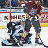 Chicago Wolves Darren Archibald attempts to block Milwaukee Admirals goaltender Jeremy Smith's view