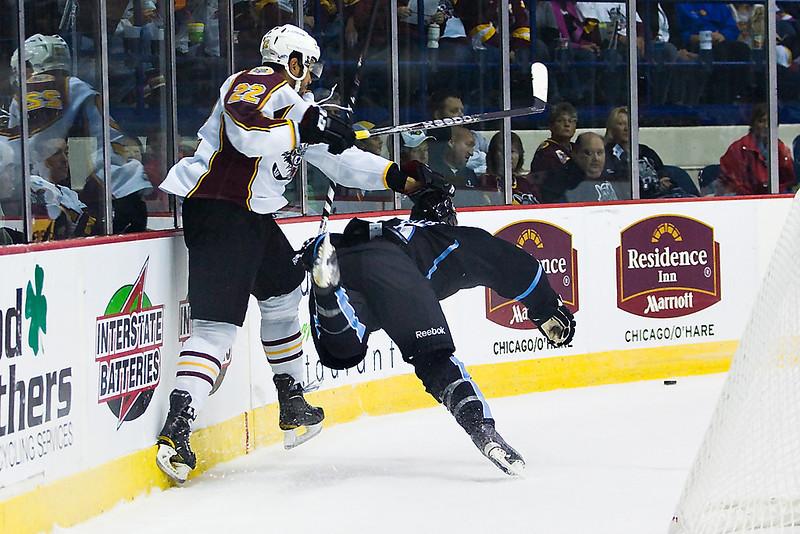 Chicago Wolves #22 Darren Archibald knocks Milwaukee's #6 Ryan Ellis to the ice