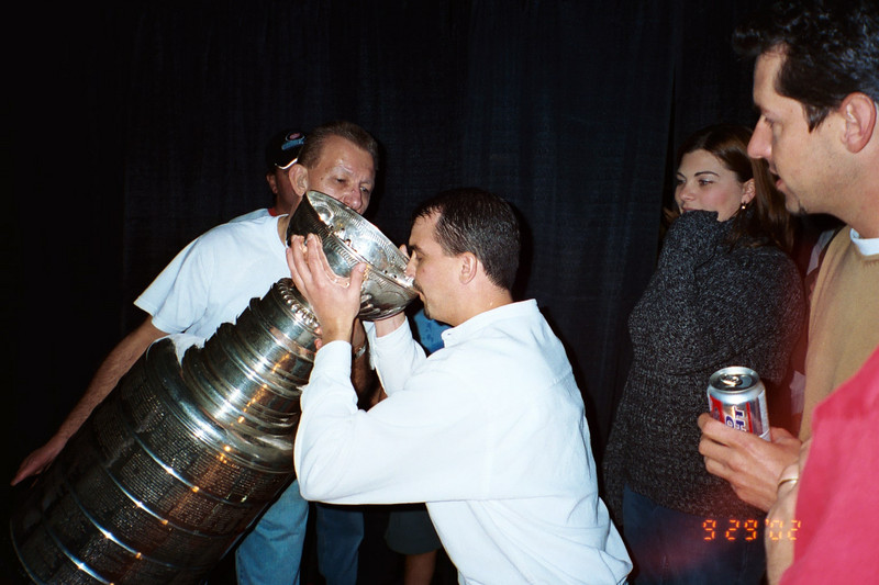 Dave drinking champagne from the Stanley Cup