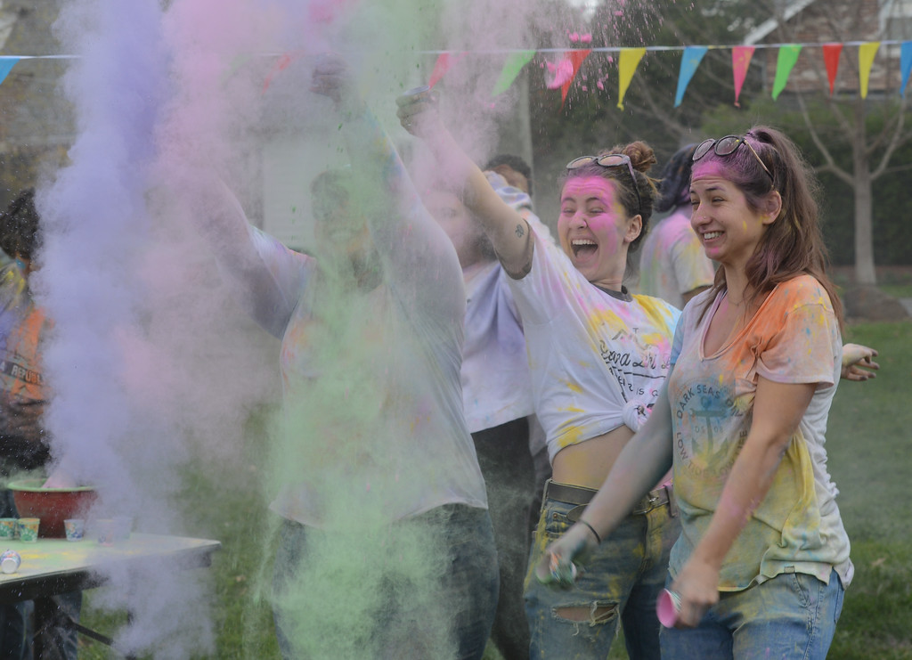 . Ladaijha Owens, Maddalena Farniati and Marissa Mcinerny throw colored powder in the air during the Holi Festival, Saturday, March 10, 2018, in Chico, California. (Carin Dorghalli -- Enterprise-Record)
