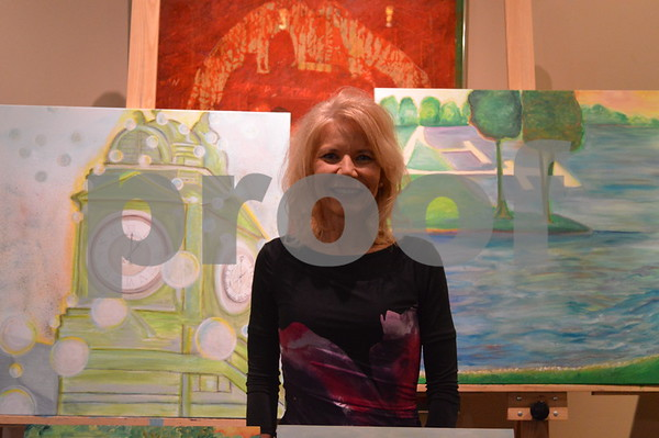 Diane O'Hern poses with two of her paintings.
