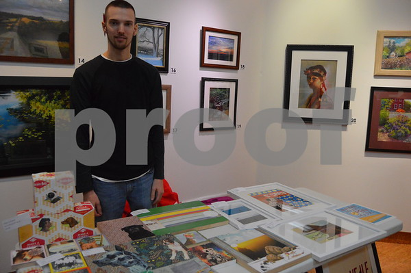 Cord McMahon poses with his collage and screen print pieces.