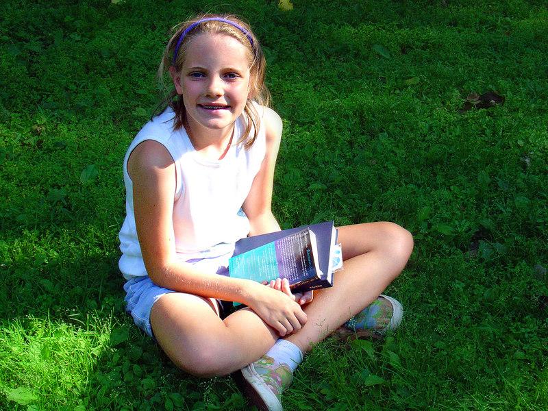 Emily enjoys a good book at the park.
