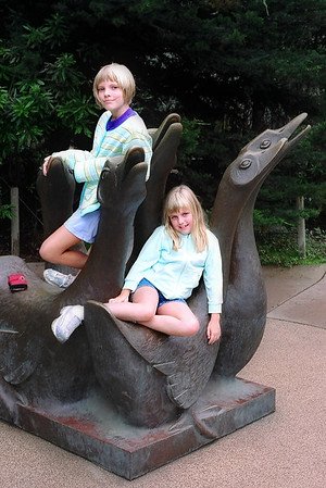 The girls on a very cool zoo sculpture.