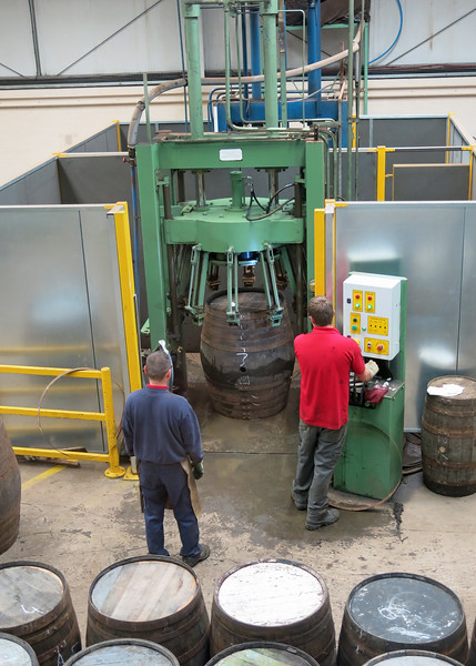 The bands that hold the barrel together are given a final tightening by a machine.